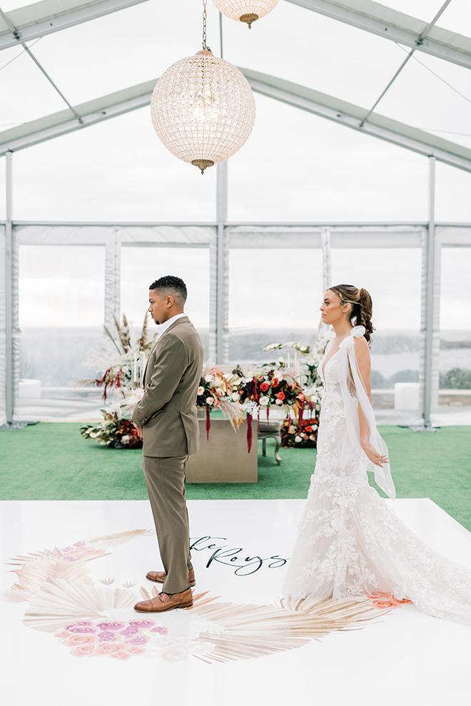 The bride stands behind her groom before the first look inside a decorated tent.