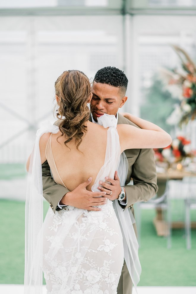 An groom is overcome with emotion during the first look, as he embraces his bride wearing a low-back Galia Lahav dress.