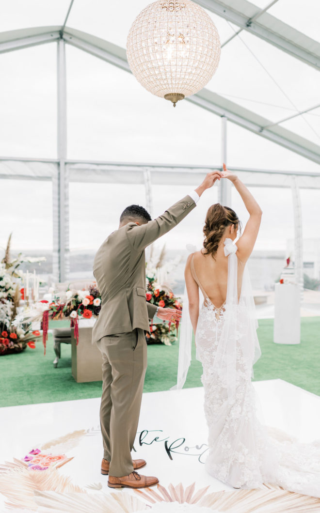 Groom in brown suit twirling a bride with a long deep v-back wedding gown underneath a statement light inside a sun dappled tented wedding space by Galveston Bay.