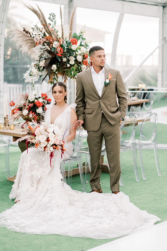 A beautiful bride in a Galia Lahav dress holds her vibrant bouquet while sitting next to her groom in a taupe suit.