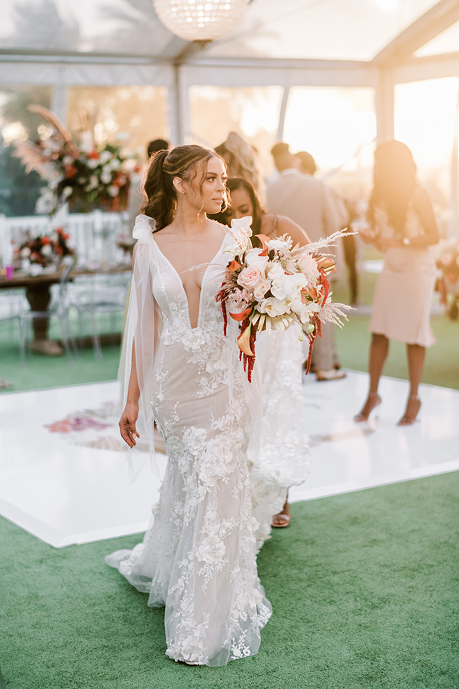 As the sun starts to set, the bride walks off the dance floor holding her bouquet as light illuminates her from behind.