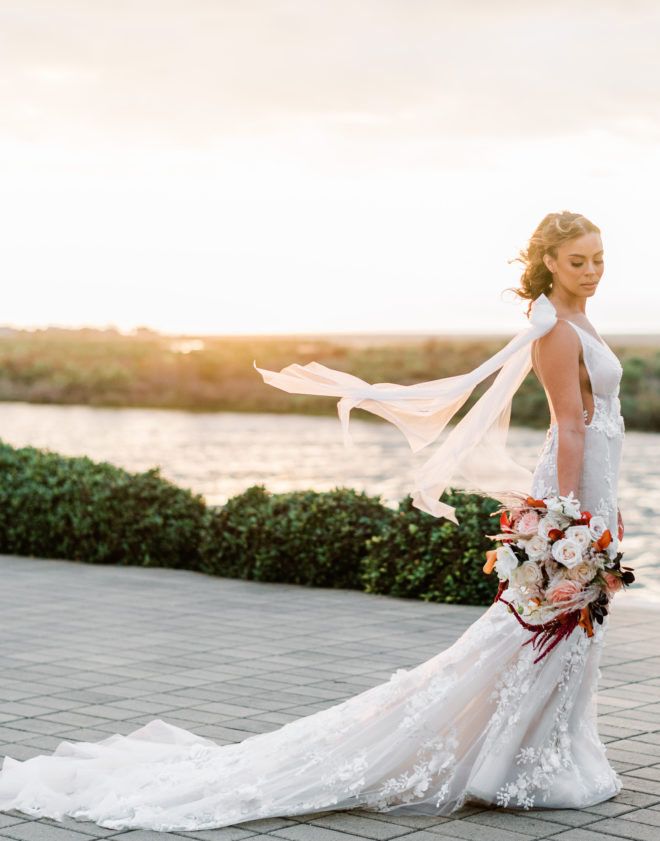 Bride in Galia Lahav fitted gown with long sweeping train and long sleeves blowing in the wind while holding a lush bouquet of sunset-hued florals with the waters of Galveston Bay behind her during the sunset hour.