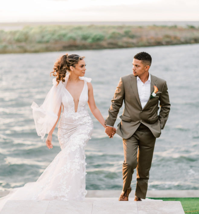 Bride in plunging neckline wedding gown by Galia Lahav holding hands with a groom while walking up a set of outdoor stairs with Galveston Bay behind them.