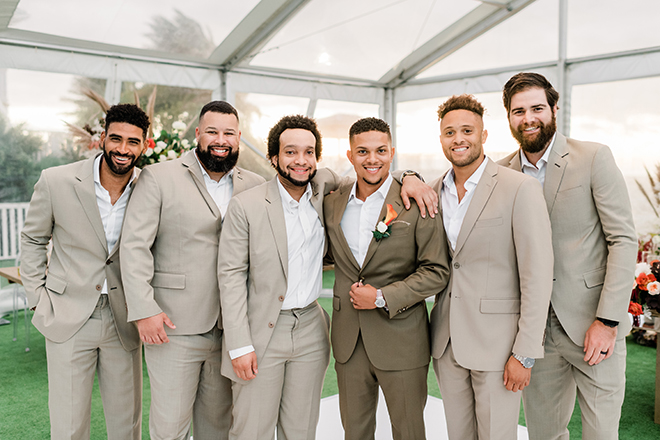 The groom in a taupe suit wears an orange boutonniere surrounded by groomsmen in light tan suits.
