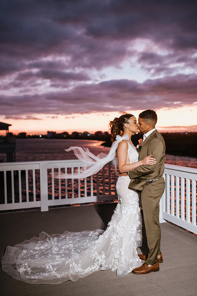 The bride and groom exchange a kiss on the balcony of the Galveston Bay-side home as the sunset paints the sky rich shades of purple, orange, and peach.