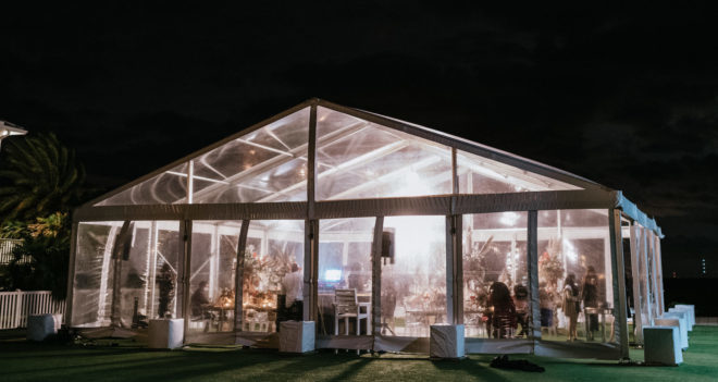 Outdoor clear tent at night during a wedding reception on a private property on Galveston Bay.
