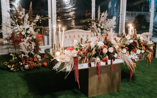 Head table with khaki colored settee set behind a gold mirror top tabled adorned with pampas grass, greenery, orange, white, red and blush roses and lit tapered candles during a tented reception designed by Plants N Petals.