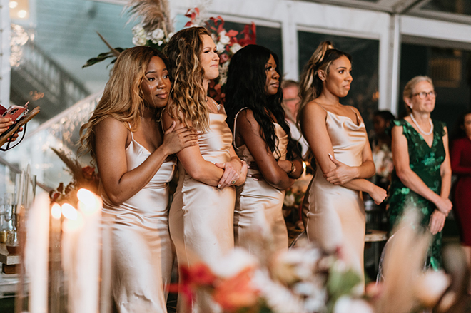 Bridesmaids in champagne midi dresses watch as their friend exchanges vows with her groom.