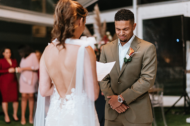 The groom gets teary eyed as his bride reads him her heartfelt custom vows.