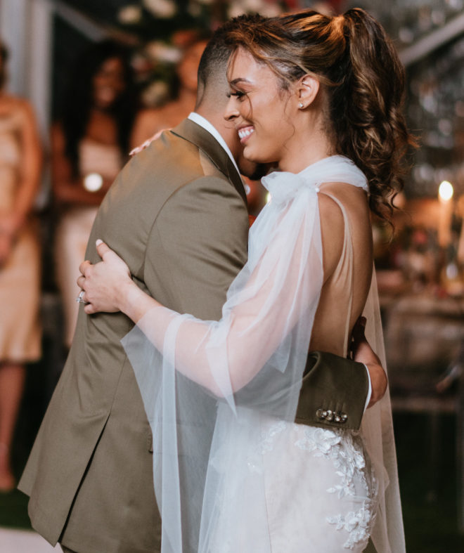 Groom and bride dancing closely while bride smiles during a tented wedding reception on Galveston Bay