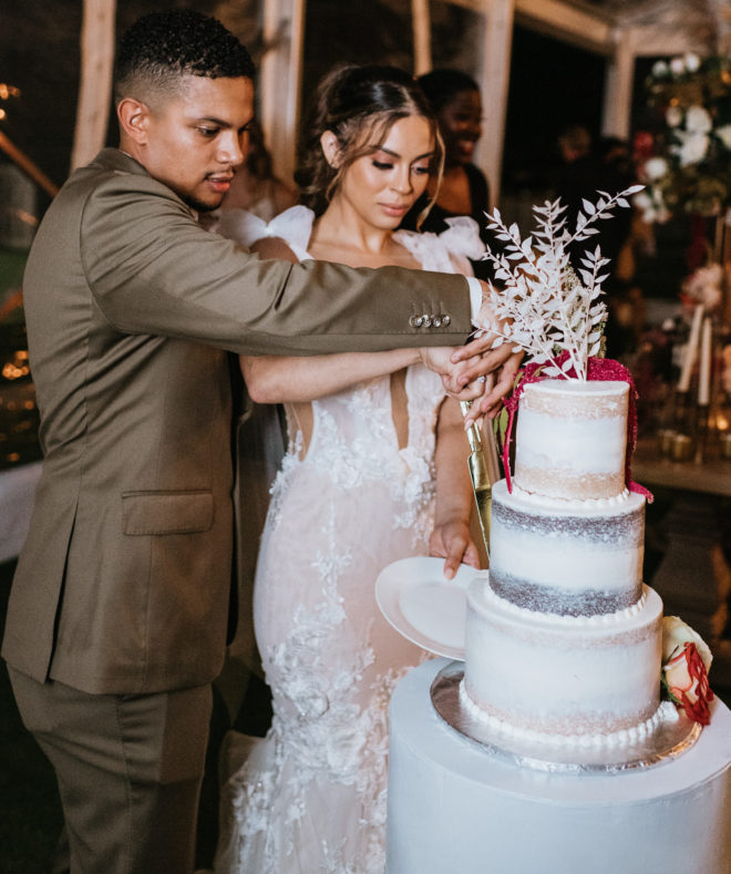 Groom and bride cut into a three tiered lightly iced cake with white and red botanicals atop the first tier by Houston Baker, Susies Cakes.