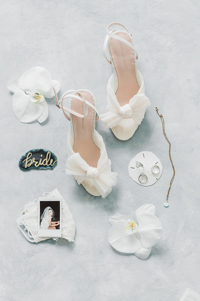 Loeffler Randall knotted bow sandals sit next to a polaroid of the brides mother, a teal slice of agate, and the wedding bands resting on a sand dollar.