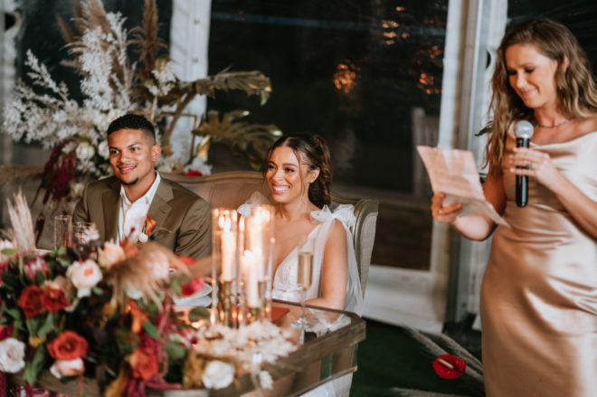 Smiling Groom and bride sitting at a mirrored head table next to the maid of honor wearing a silk blush dress holding a microphone and a piece of paper during her reception speech.
