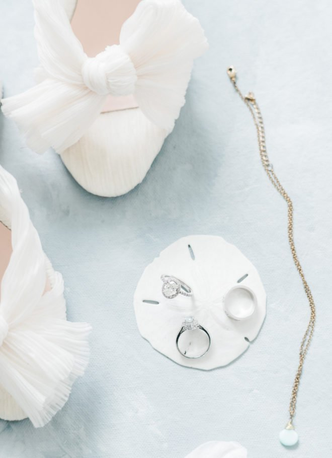 White high heels with tied bow next to diamond ring wedding and engagement ring set atop a white sand dollar and long necklace atop a light blue background.