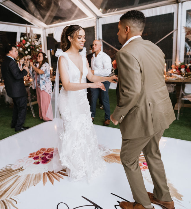 """bride in white Galia Lahav dress with tied shoulder straps dances with the groom in a light brown suit on a white dance floor that reads the couples last name, """"The Roys"""" inside their tented reception in Galveston."""