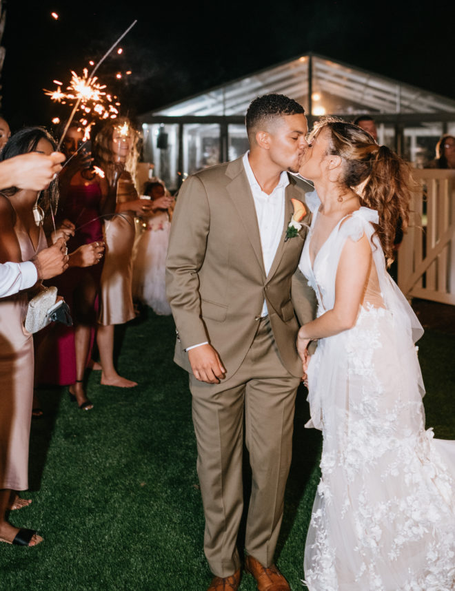 Bride and groom kissing during a night time sparkler send-off outside the tented wedding reception on a private property next to Galveston Bay in Texas.