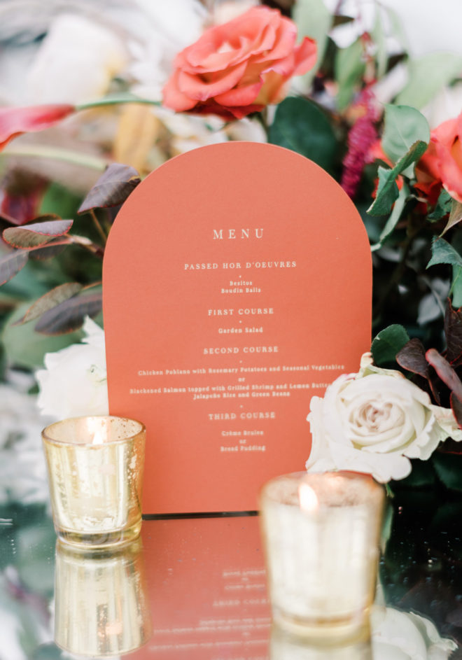 """Coral colored half circle menu that reads, """"Menu"""" and """"Passed Hor Doeuvres"""" nestled between coral, blush and orange florals and two gold lit candle votives in an intimate tented ceremony designed by Plants N Petals."""
