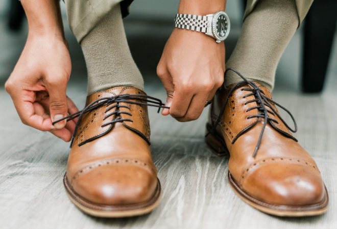 Groom with silver watch on his wrist tying the laces of light brown loafers.