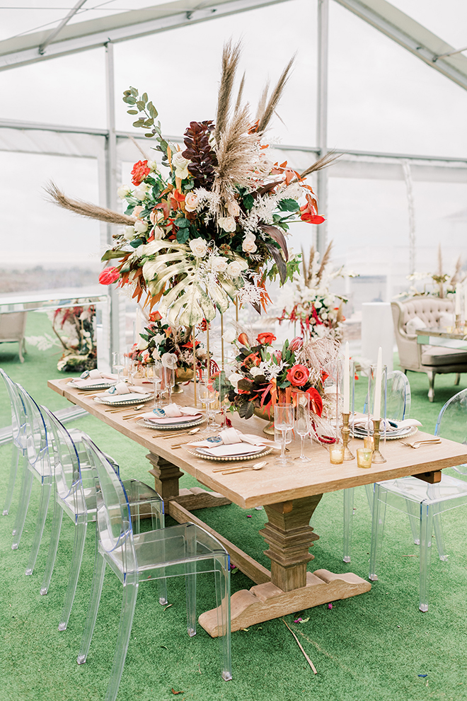A beautiful tablescape at this sunset colored wedding is bursting with vibrant, cascading floral arrangements boasting orange, red, and blush blooms.