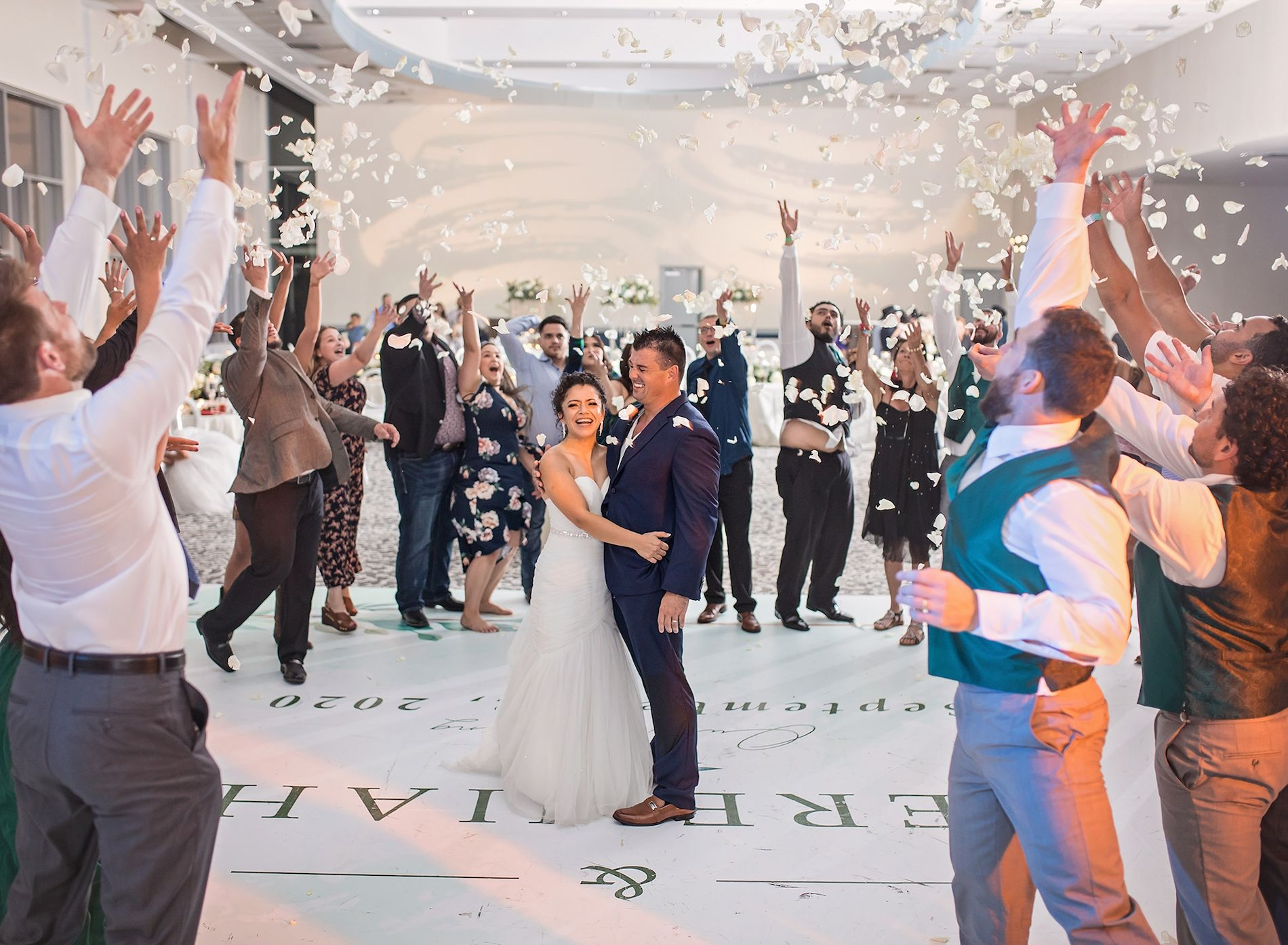 Friends and family circle around the bride and groom on the dance floor and throw white rose petals up in the air towards them to celebrate.