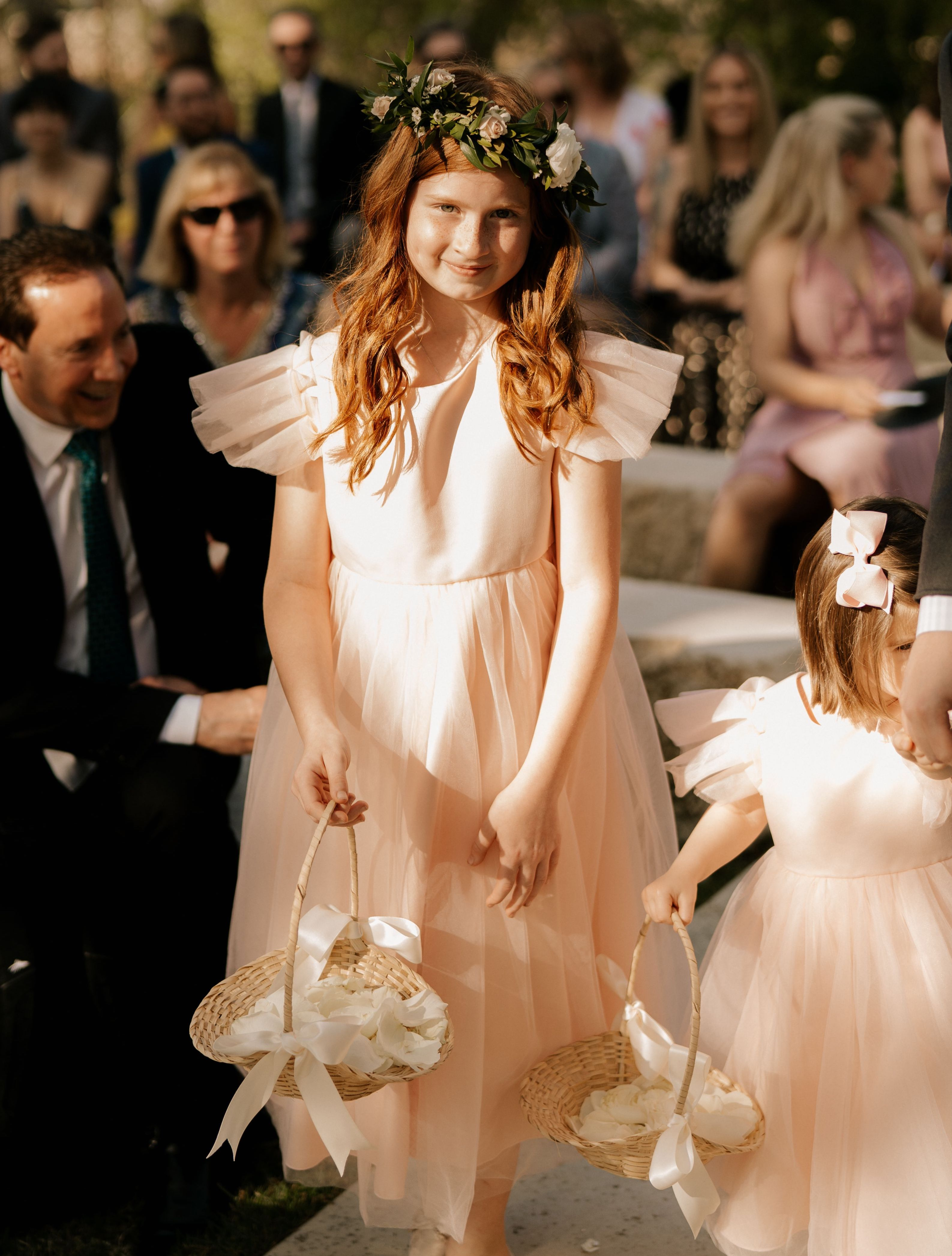 An adorable flower girl walks down the aisle wearing a floral crown and blush flowy dress.