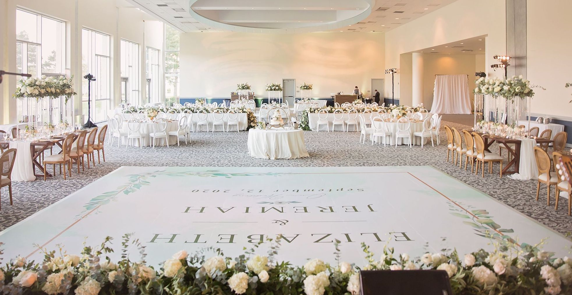 The Del Lago ballroom at the Margaritaville Resort, Lake Conroe is decorated in white rose and eucalyptus floral arrangements, off-white linens and a white dance floor with a personalized decal of the bride and groom's name.