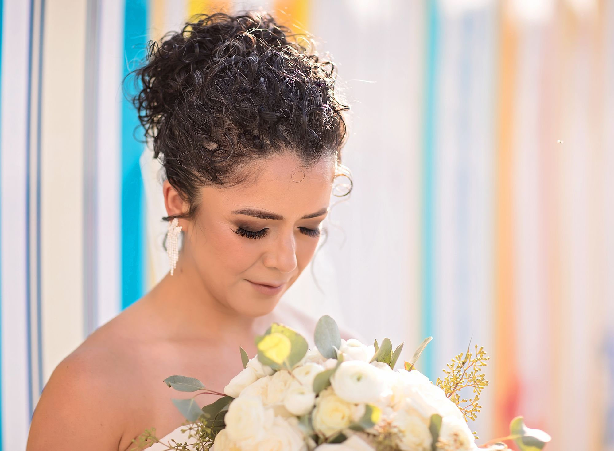 A bride tilts her head down looking at a bridal bouquet in front of a colorful array of classic surfboards at her lakeside wedding at Margaritaville Resort, Lake Conroe.