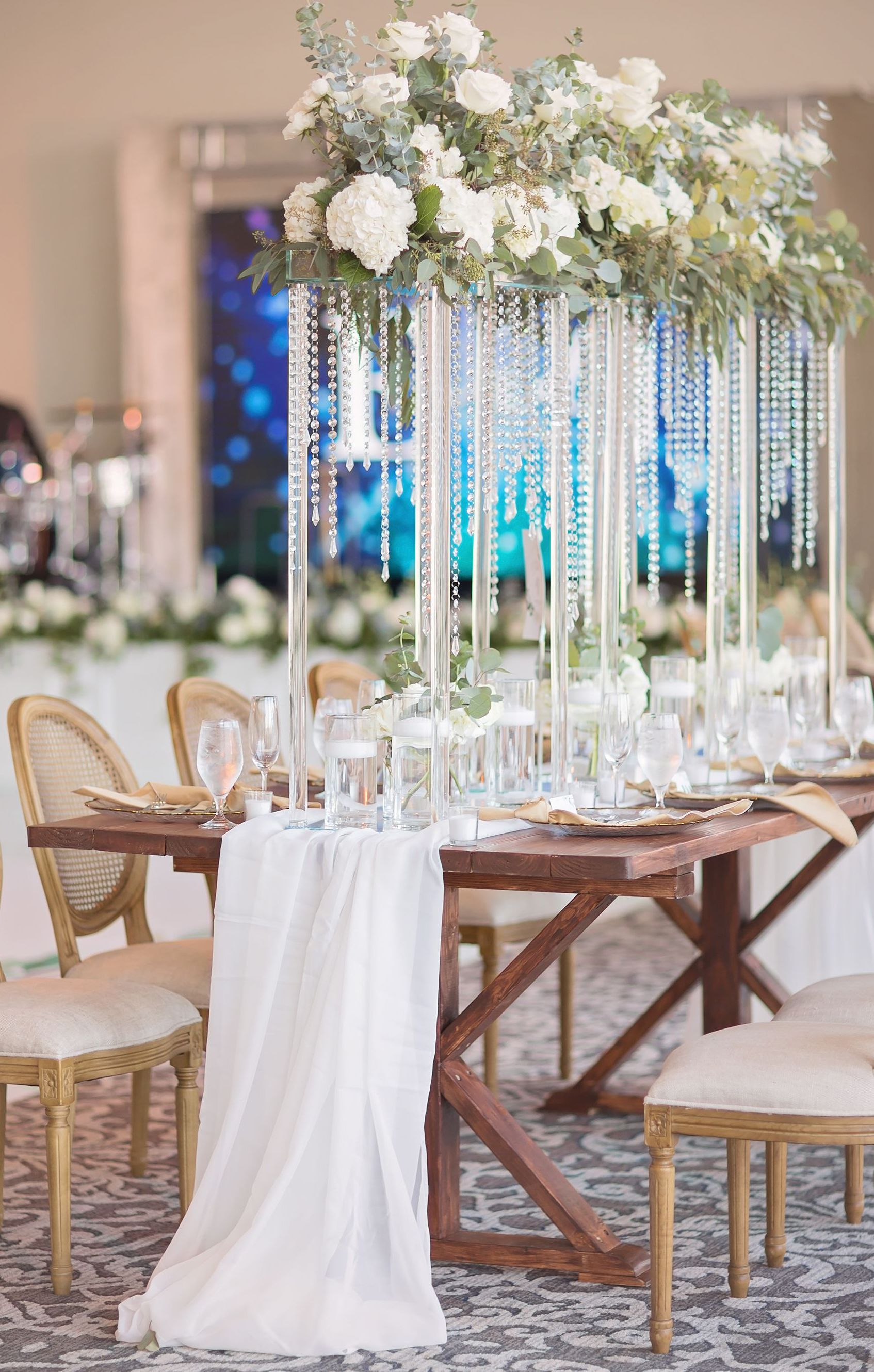 Crystal glass reception decor is set up in the center of the table, including a long white table runner, floating candles, small singular candles, white rose and eucalyptus floral arrangements, and hanging crystal beads.