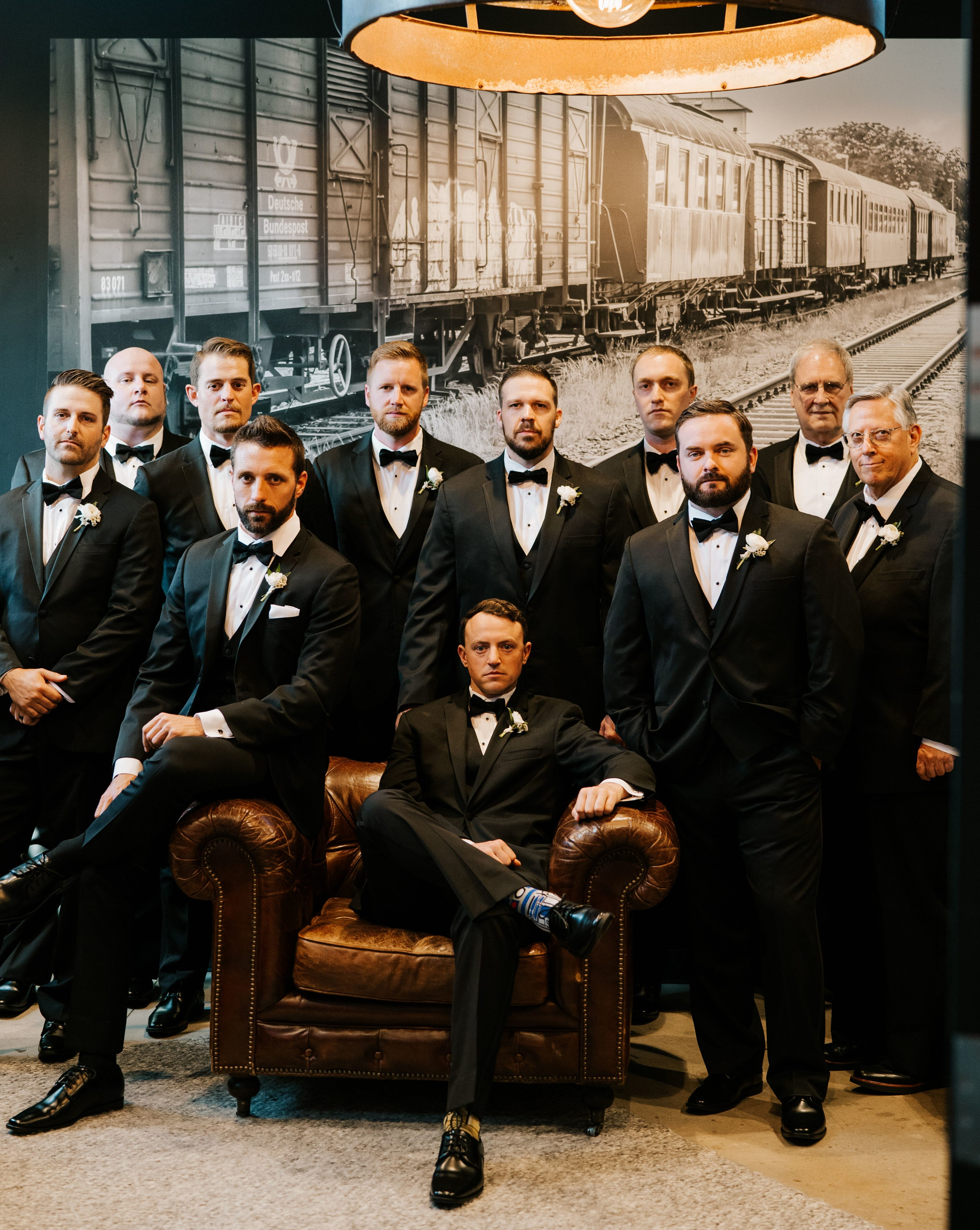 The groom sits in a leather armchair surrounded by his groomsmen, all in black Tuxedos.