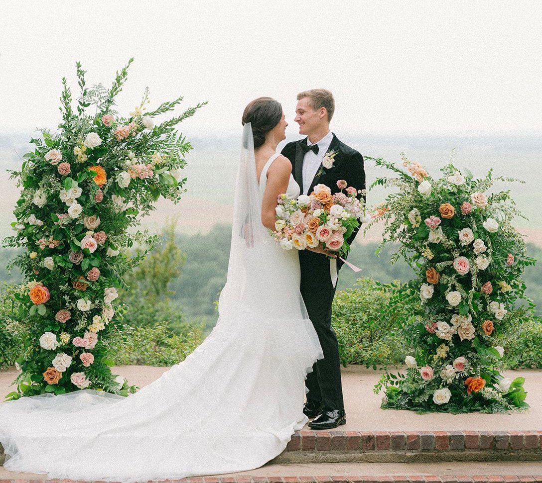Bride and groom stand at the alter for their artfully curated Southern wedding. Bride is holding her bridal bouquet and there is a beautiful view of the hill country.