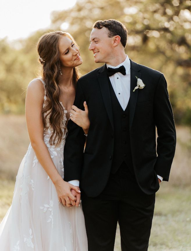 Bride and groom gaze into each other's eyes while holding hands with trees and grass behind them after their wedding ceremony in Spring Branch, Texas.