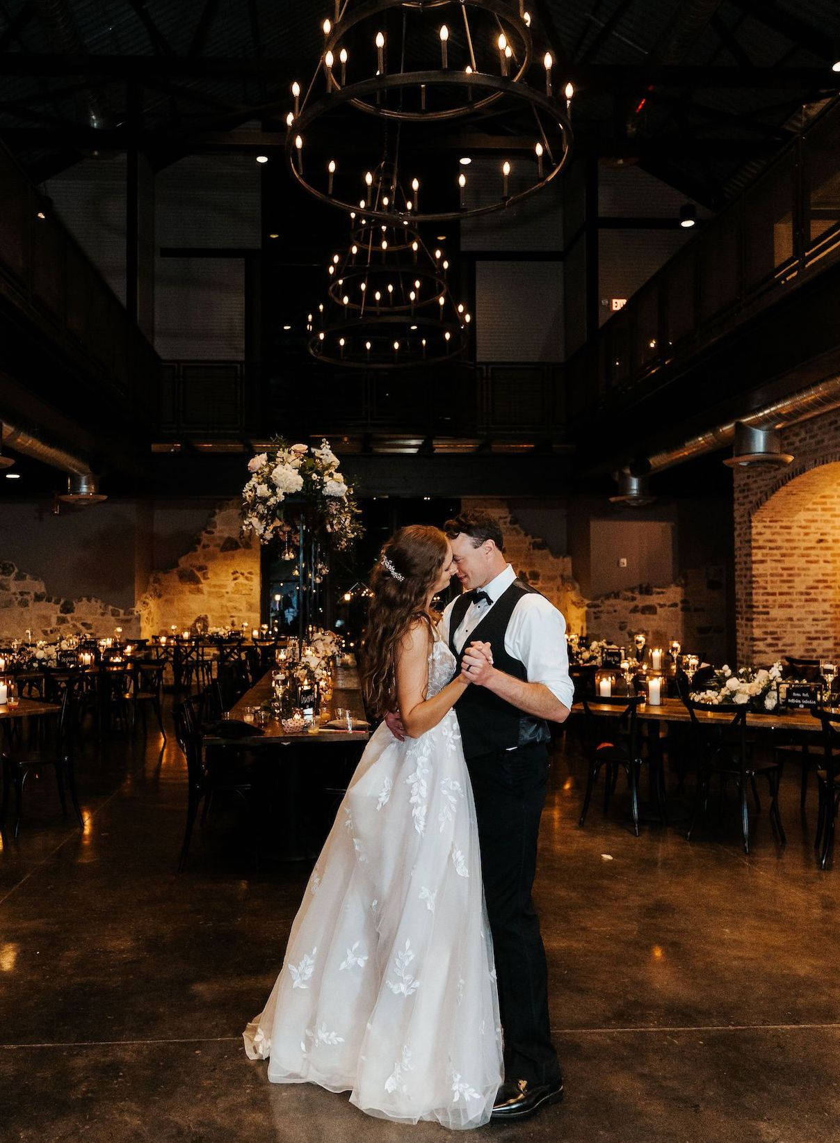 A beautiful couple shares a last dance in their empty reception venue, illuminated by candlelight and soft light from iron chandeliers.