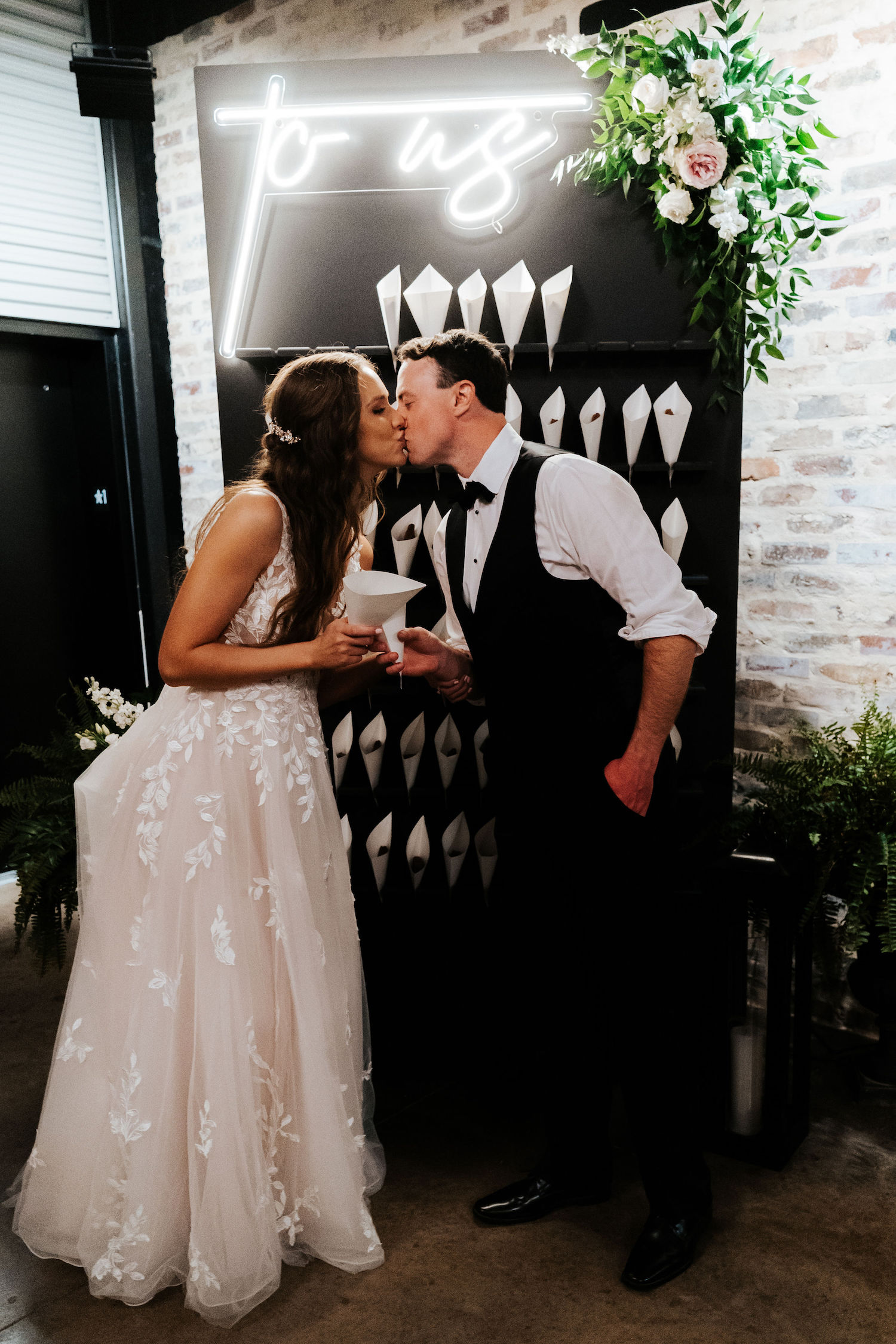 """The newlywed couple exchanges a kiss in front of their custom brownie wall adorned with florals and a neon sign that reads """"to us."""""""