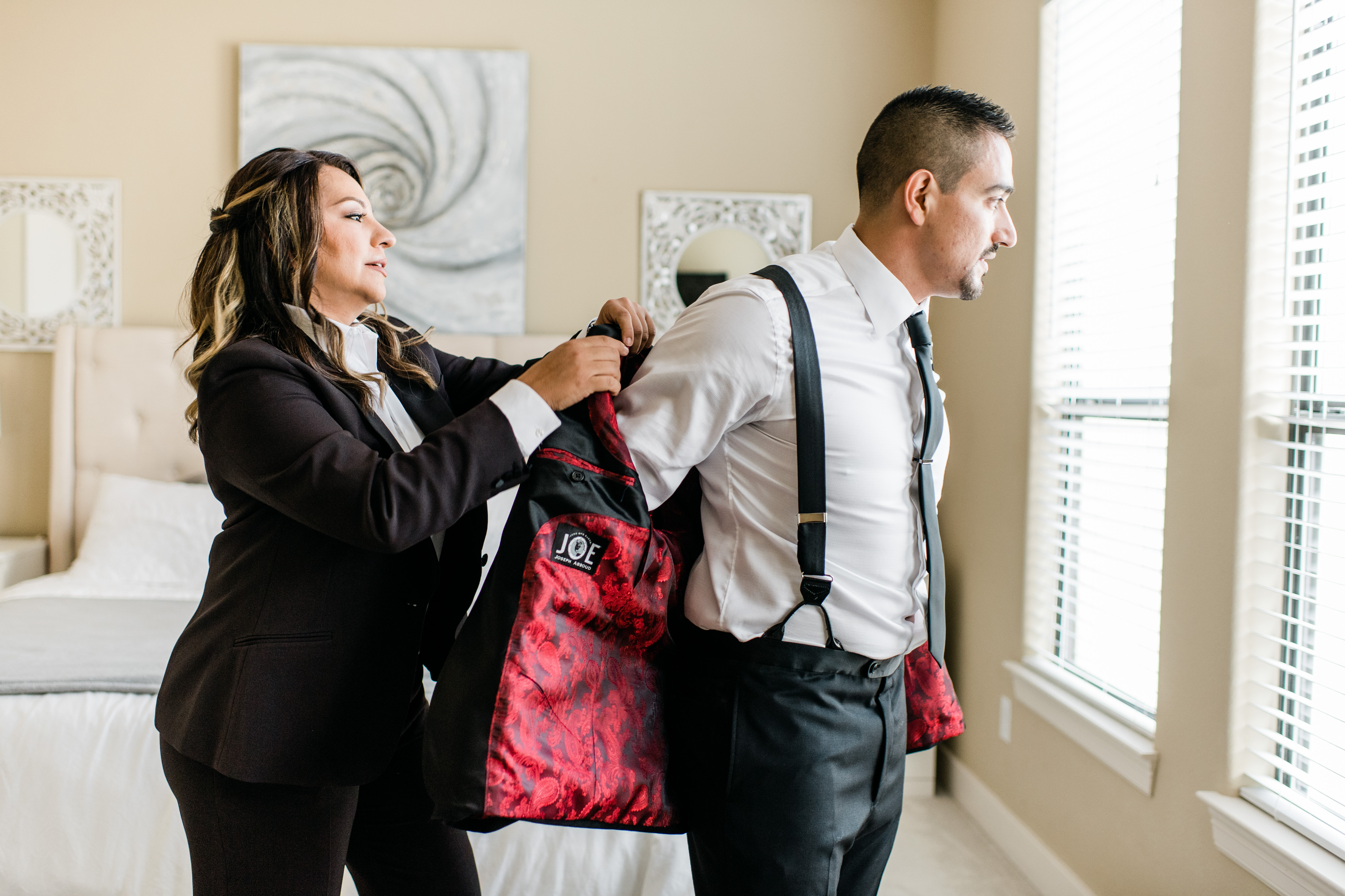 The groom's sister helps him put on his suit jacket.