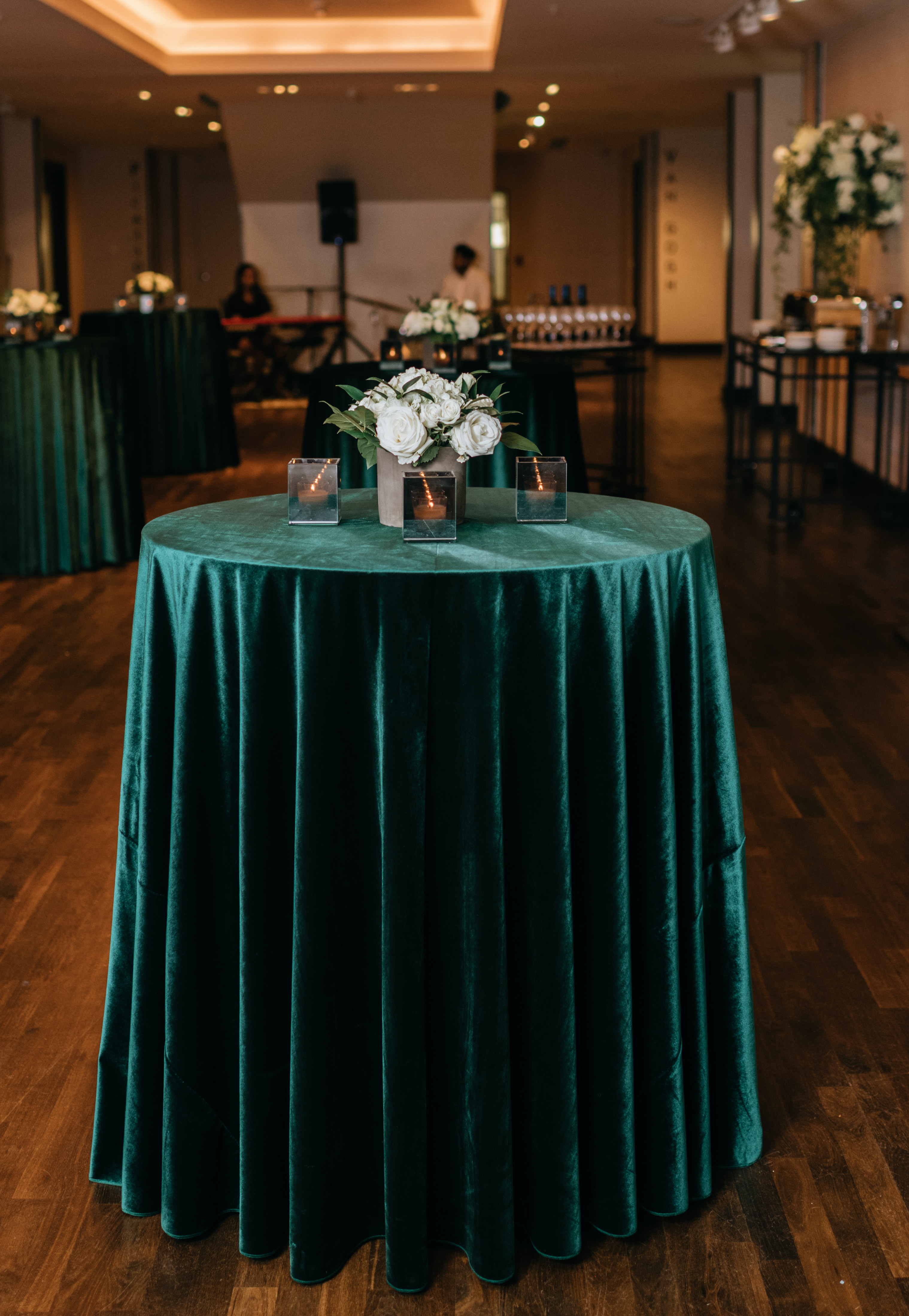 A velvety green table-cloth is draped over the cocktail table.