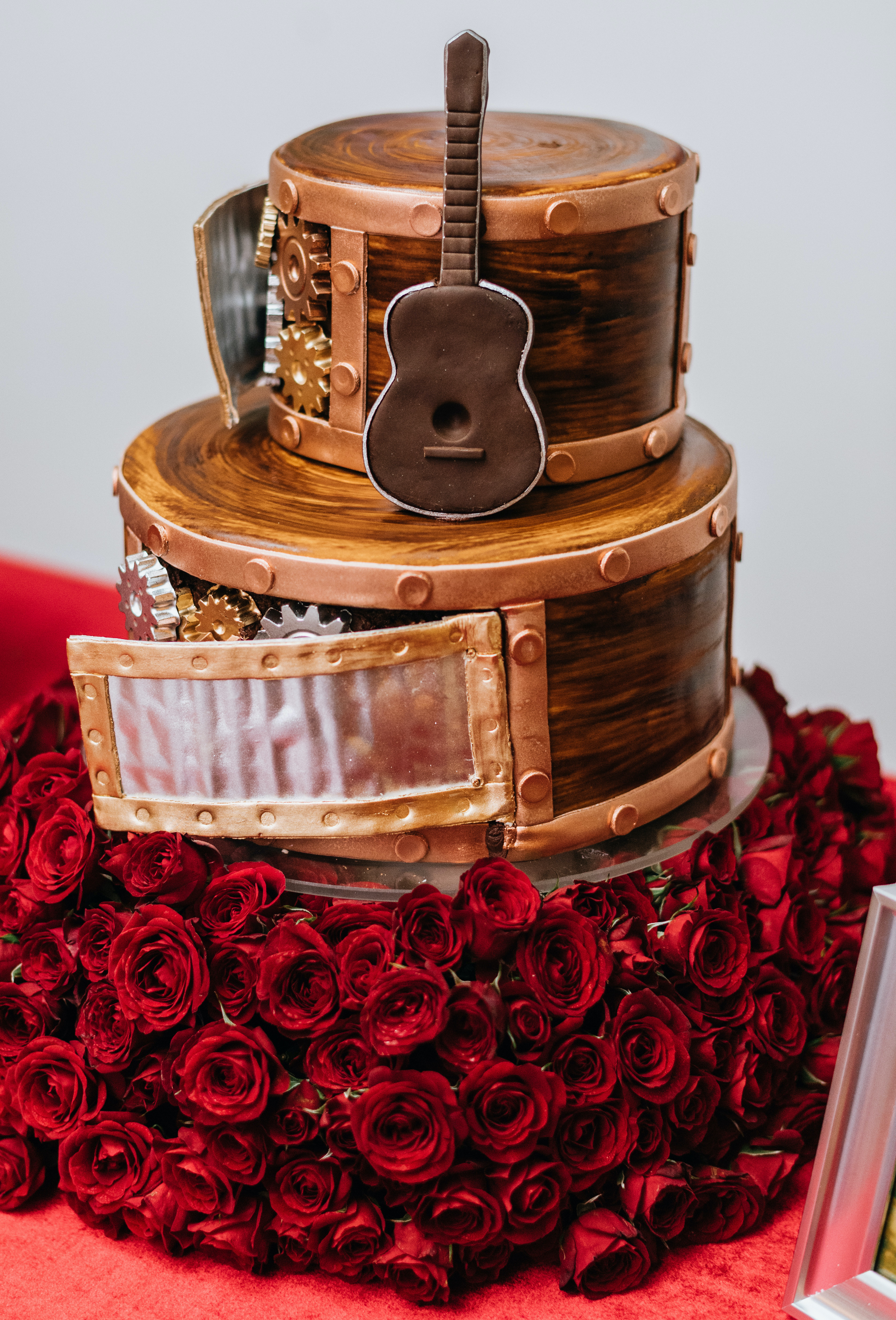 The groom's cake has a guitar on it and red roses surrounding the base.