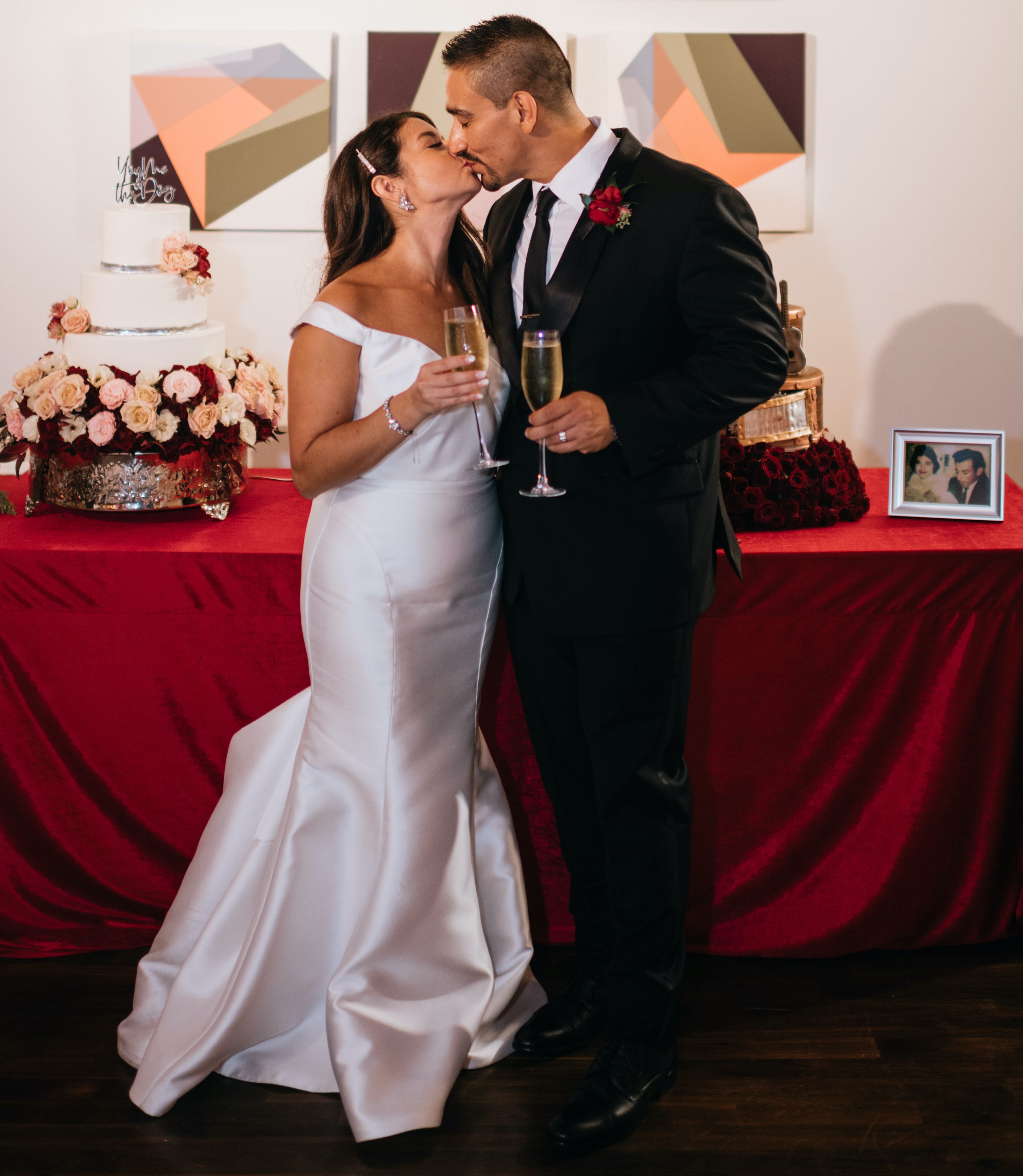 The bride and groom hold champagne as they kiss in front of their wedding cakes.