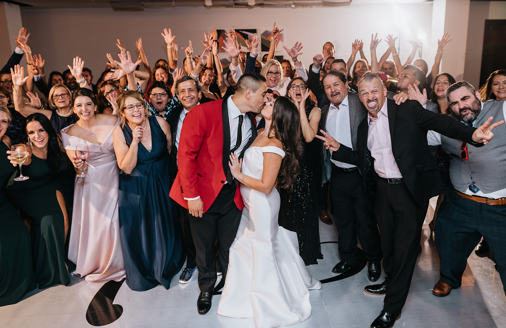 The bride and groom kiss on the dance floor with their wedding guests all behind them.