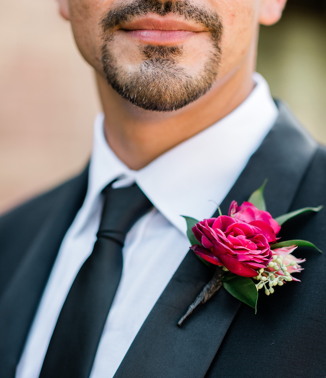An up-close photo of the groom's ruby red boutonniere.