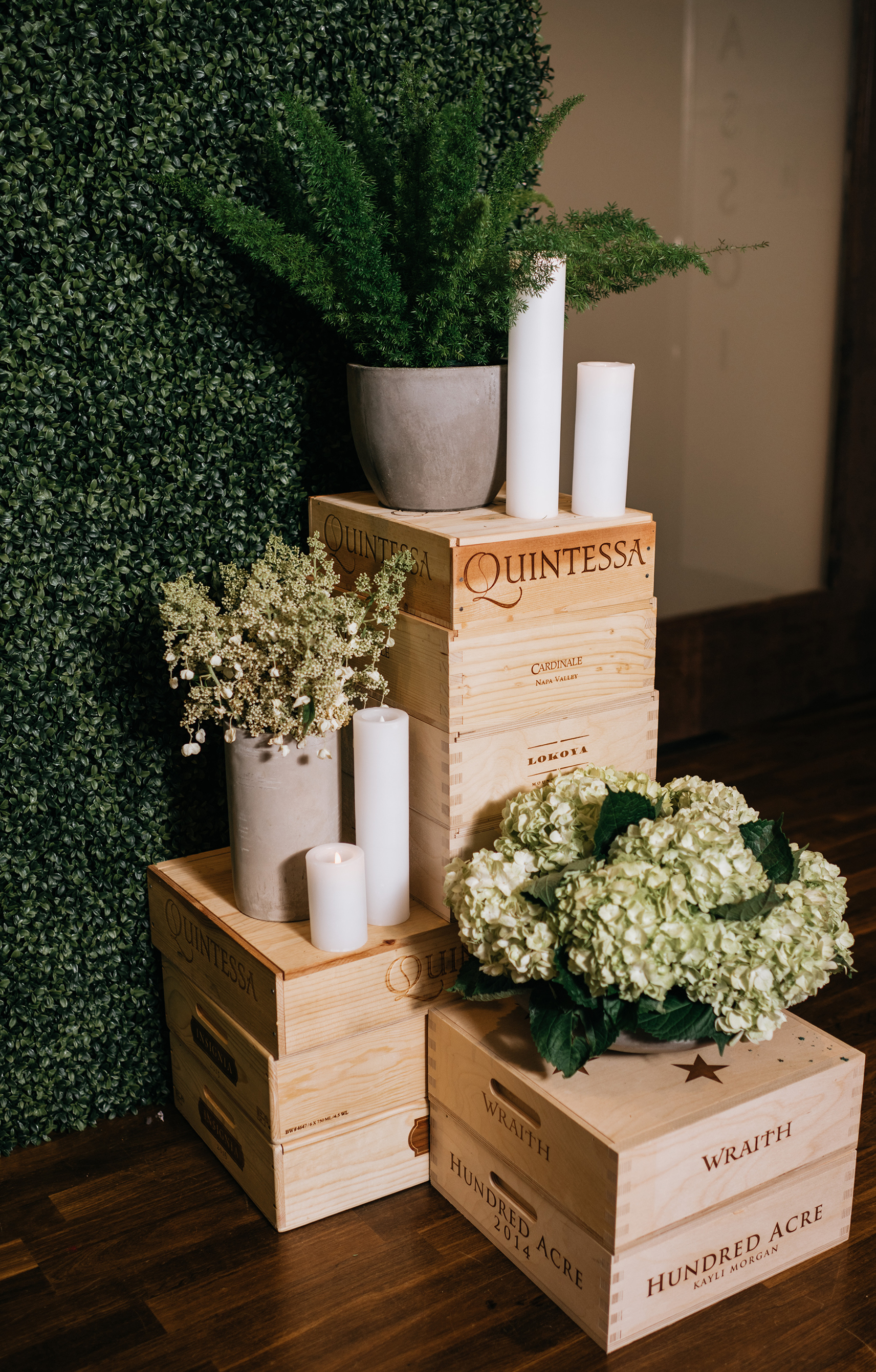 Wine barrels act as wedding decor with the greenery.