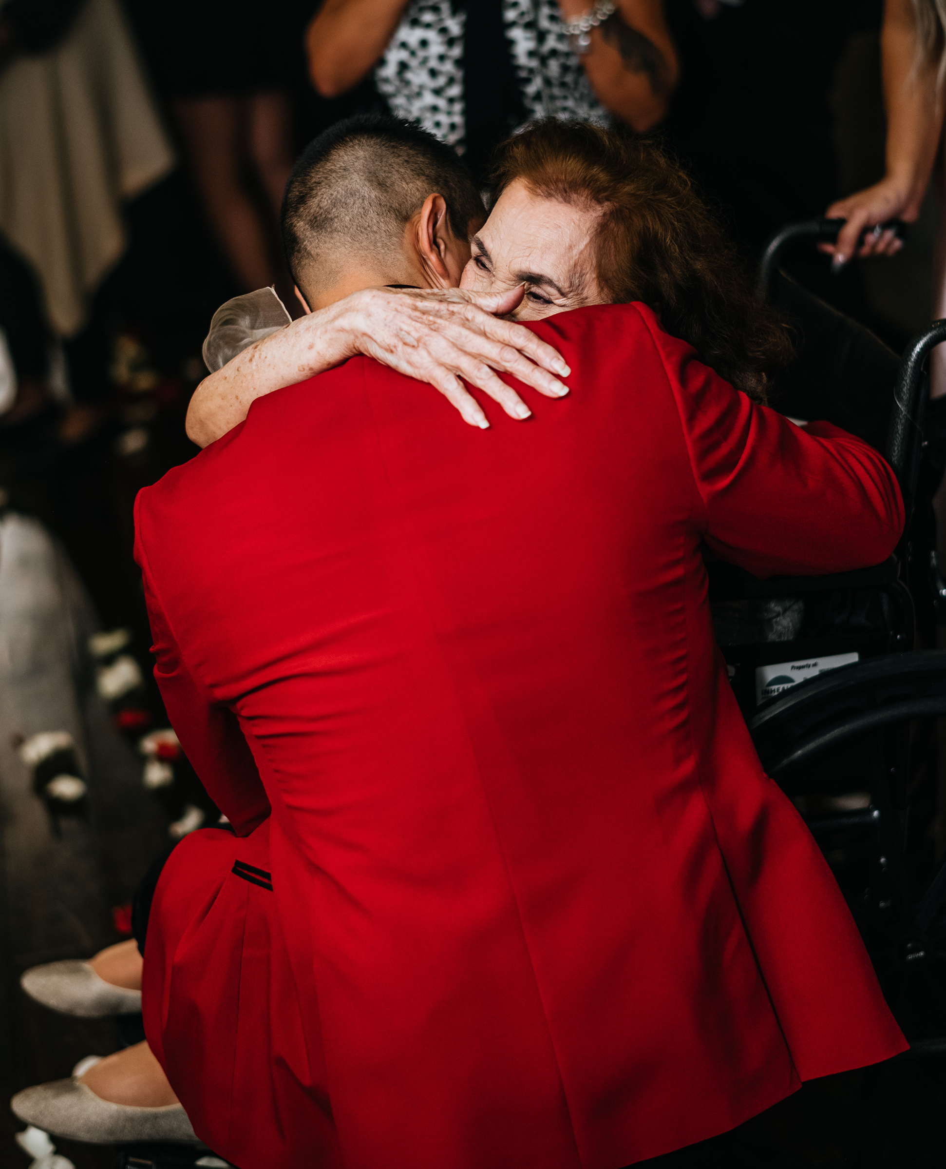 The groom is in a ruby red suitecoat hugging his grandmother who is in a wheelchair.