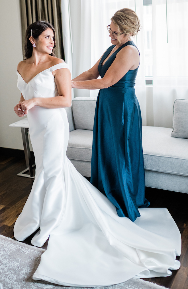 The bride smiles at her mom as she is putting on her wedding dress.