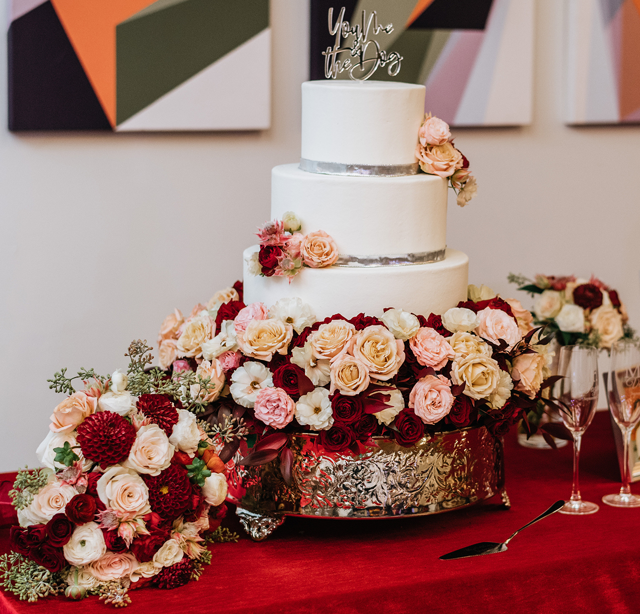 The wedding cake is surrounded with ruby red roses and beige and pink filler flowers.