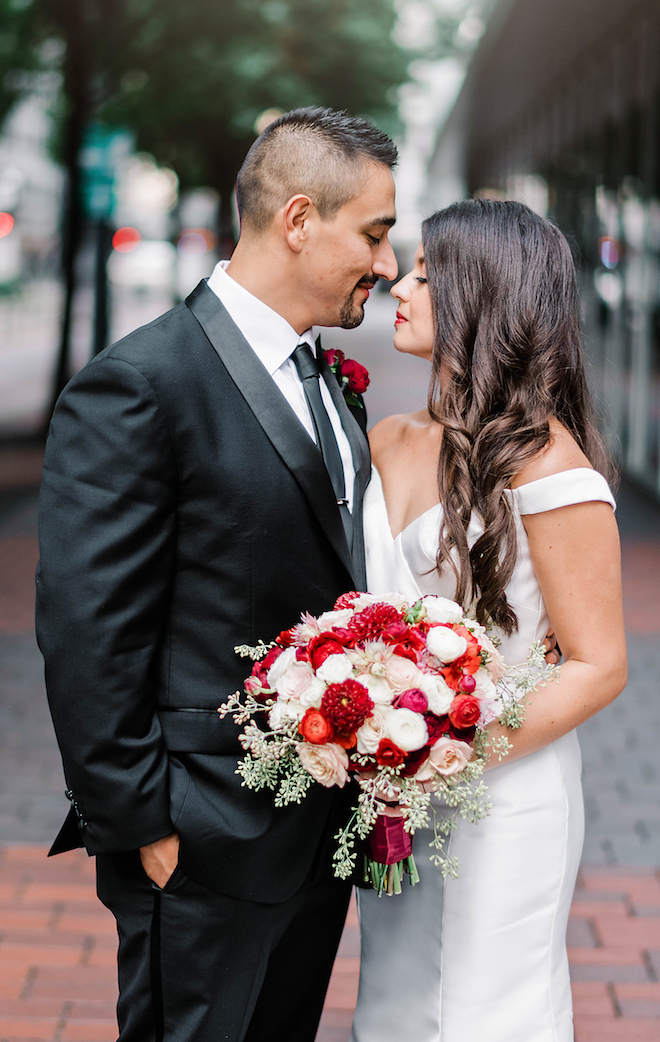 Bride is holding her ruby red bridal bouquet with her husband by her side.