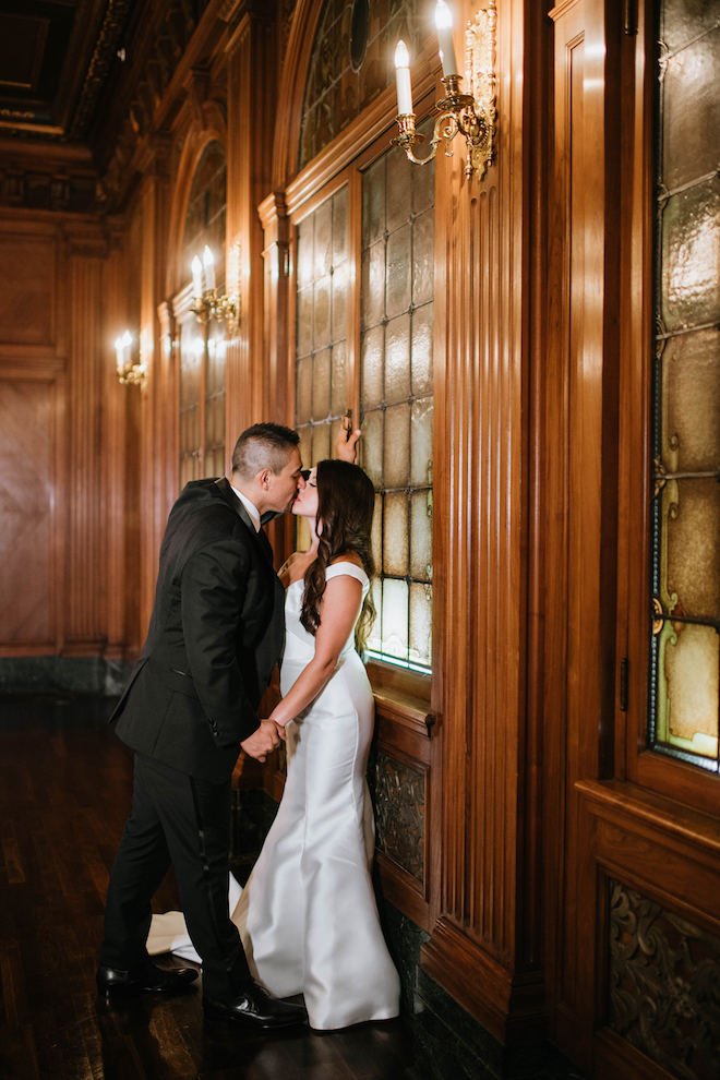 The bride and groom kiss in a romantically candle-lit hallway