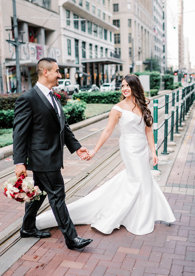 Bride and Groom holding hands walking through the city.