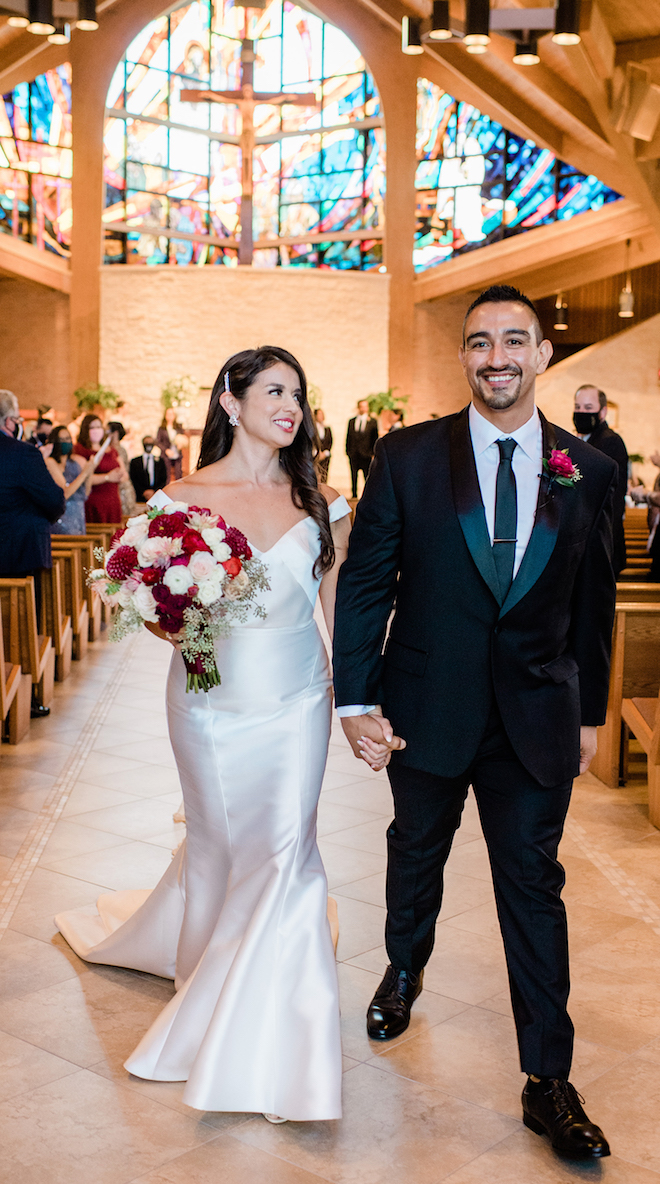 The bride, holding a ruby red, blush and ivory bouquet, holds hand with a groom in a black tuxedo after their wedding ceremony in Houston, Texas.