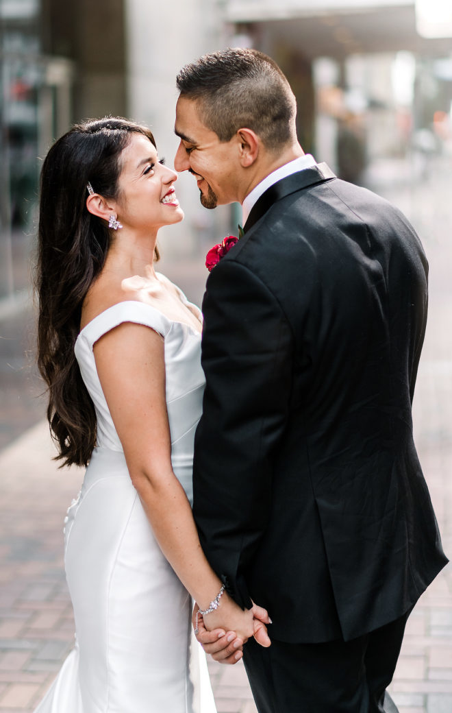 The bride and groom hold hands and smile at each other outside of JW Marriott Downtown Houston. The groom has a ruby red boutonniere.