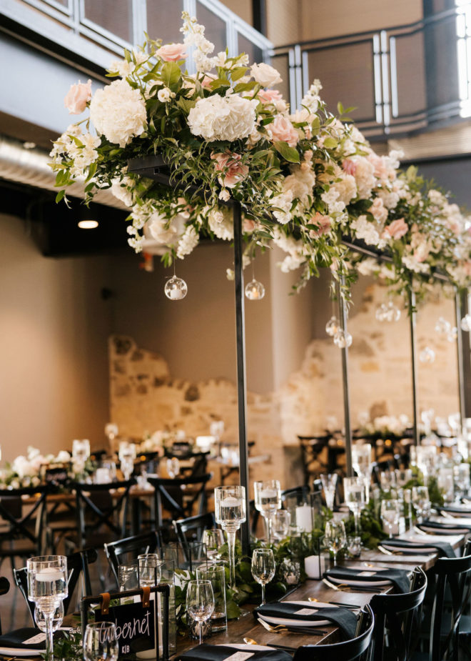 Long farmhouse table with tall hydrangea, rose and greenery floral installation inside of wedding venue, Park 31, in Spring Branch, Texas in the Texas Hill Country.