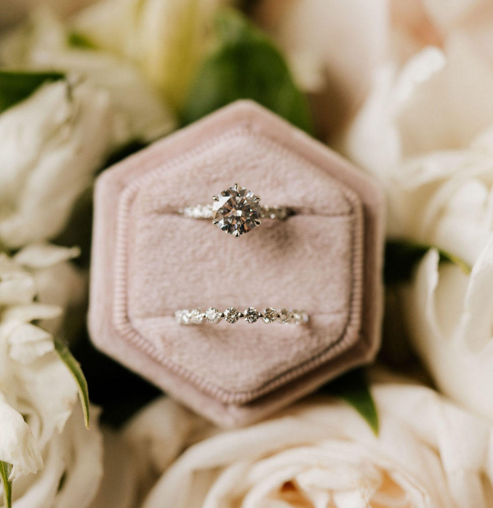 A bride's engagement ring and diamond wedding band rest in their box surrounded by white roses.